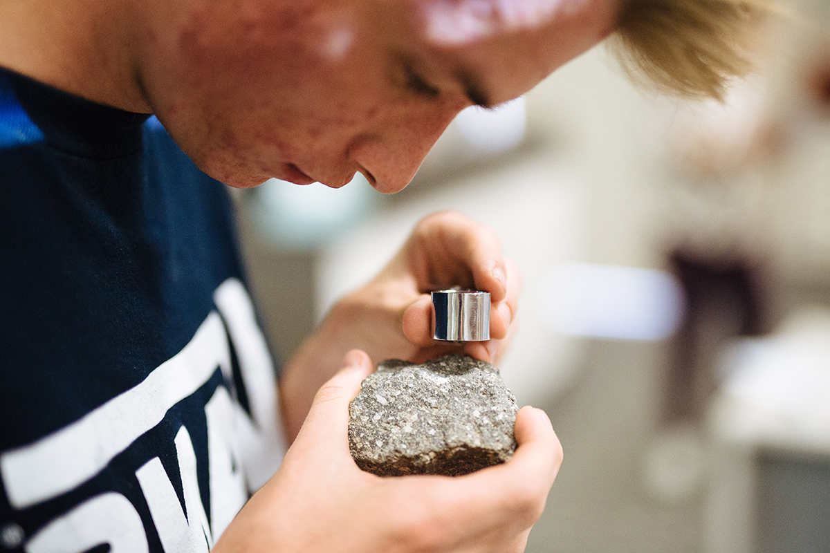 Undergraduate student using a magnifying glass to examine a rock