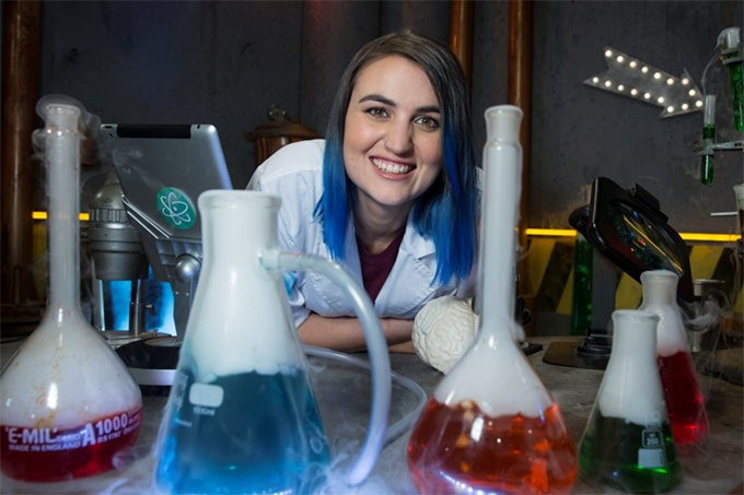 ANU alumnus, Lee Constable, smiles through test tubes
