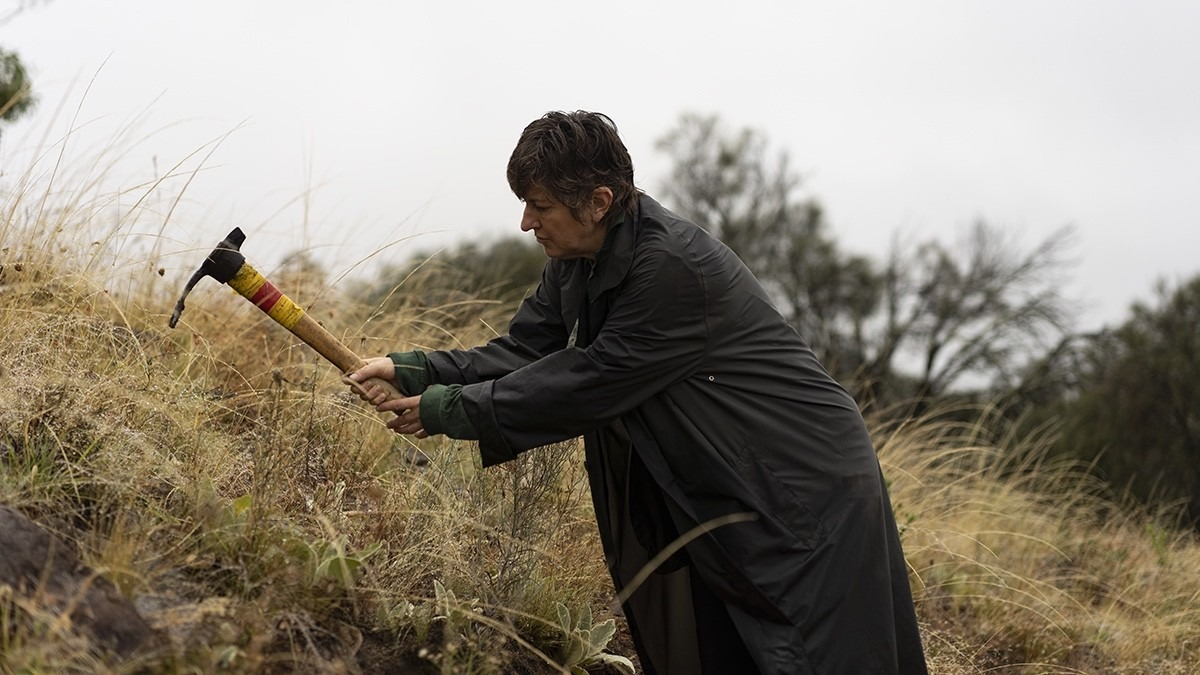 Lady in large raincoat, using mattock that looks like a large pickaxe to remove weeds from an embankment.