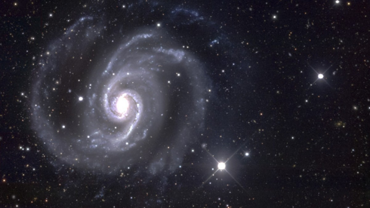 Telescope image of a spiral galaxy surrounded by white stars.