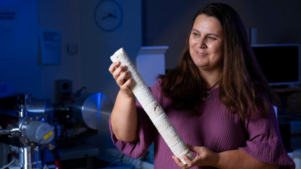 Professor Nerilie Abram is holding a coral core sample in laboratory lit with blue light