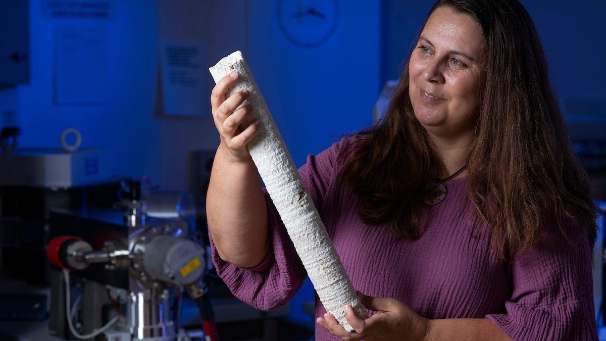 Prof Nerilie Abram holds up a coral core in the lab.