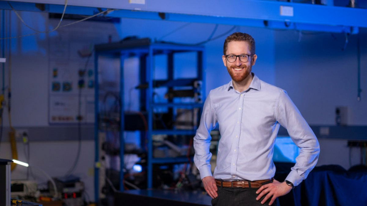Dr Andrew Horsley is standing in a lab with blue light and electronic equipment behind him