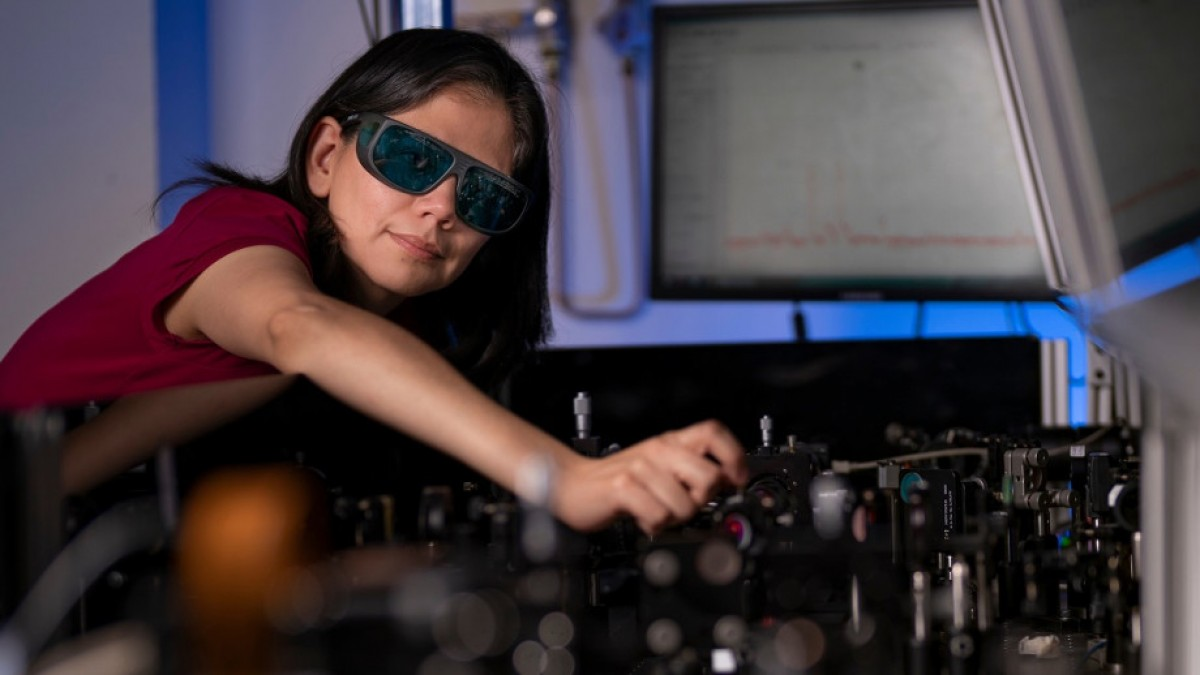 Dr Rocio Camacho Morales in physics lab, photographed leaning over a table with laser optics equipment.