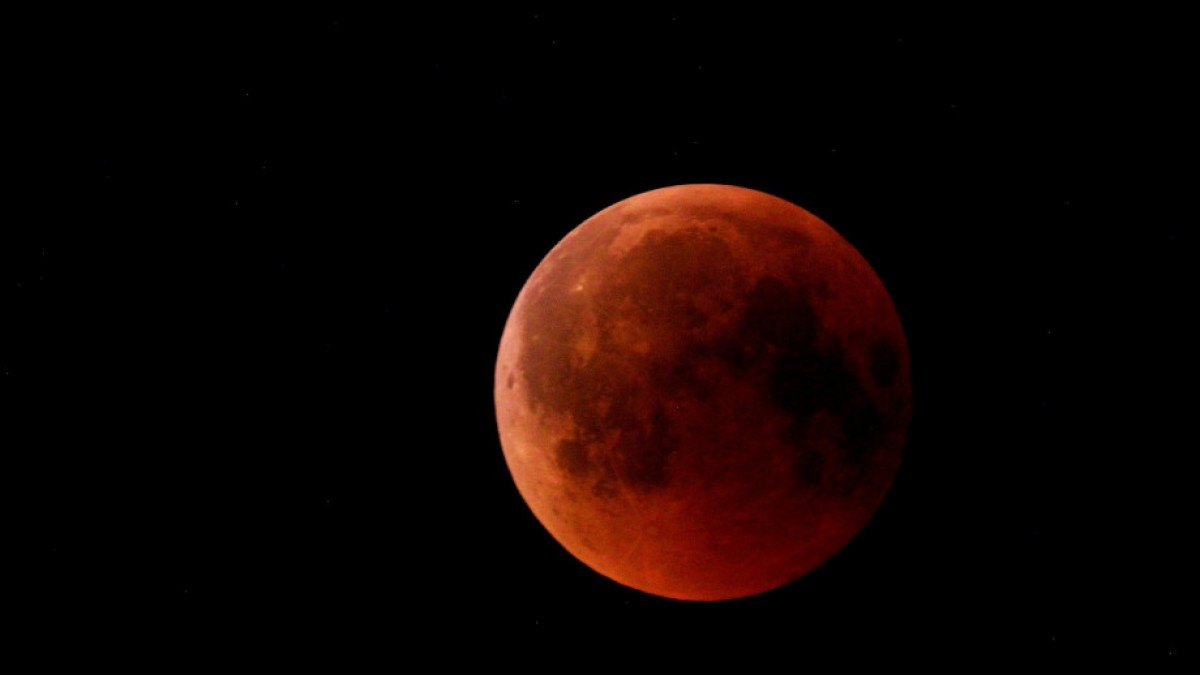 Blood red coloured full moon in night sky