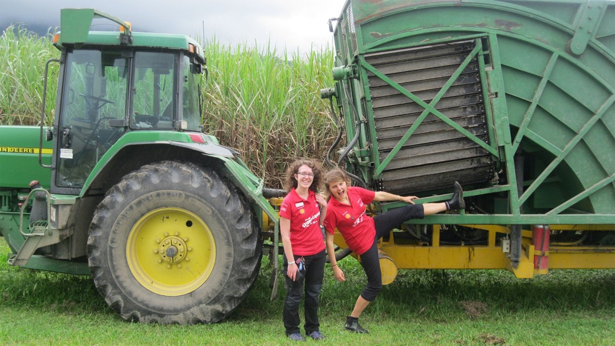 Two people wearing Questacon Science Circus shirts stand in front of a tractor in a cane field.
