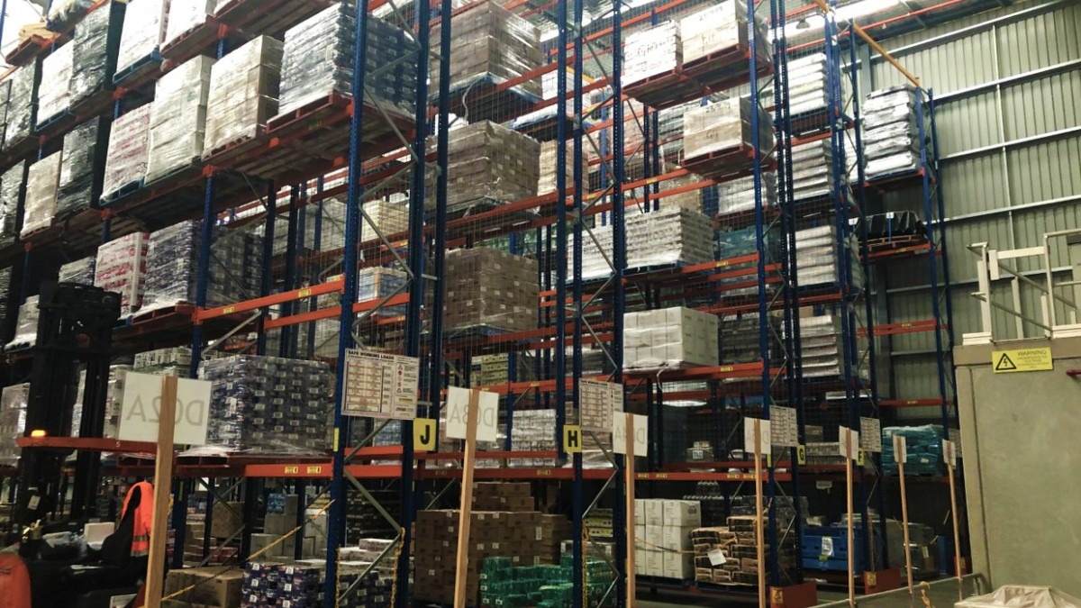 A Foodbank warehouse full of stacked food and crates.