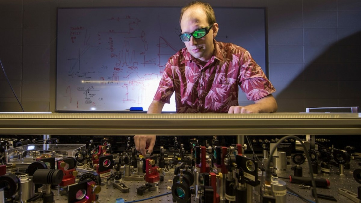 Francis Bennet is in the laboratory with sunglasses on as he tests laser optics equipment.