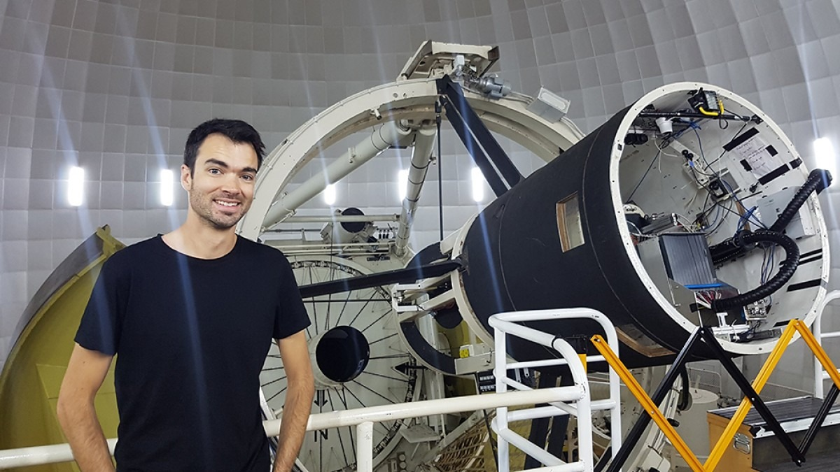 Dr James Gilbert next to telescope.
