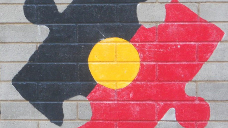 Aboriginal flag in shape of jigsaw piece, mural on wall.