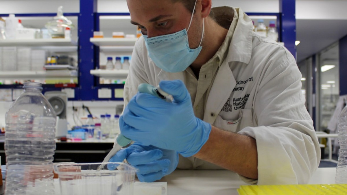 A researcher in a lab with a plastic bottle.