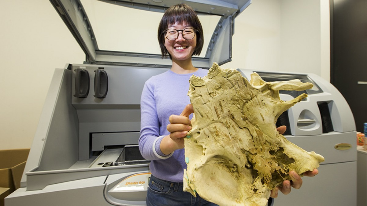 Woman holding a large jaw bone up to the camera.