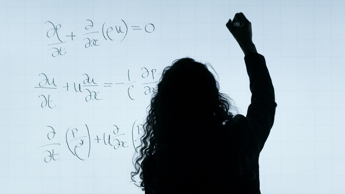 Woman writing mathematics equations